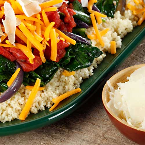 couscous piled high with sauteed spinach, tomatoes and cheese