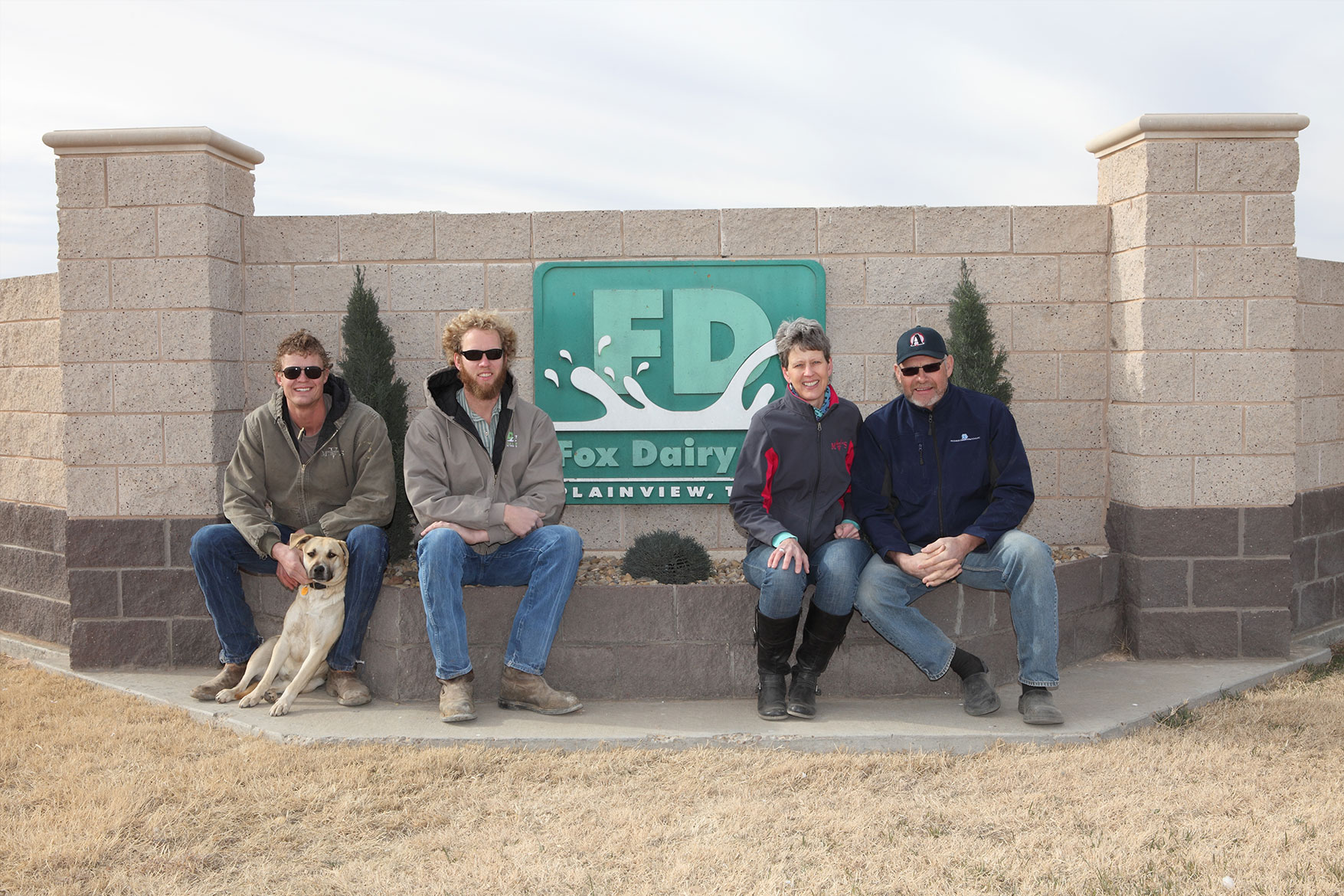The DeVos family poses in front of the sign for their dairy farm.