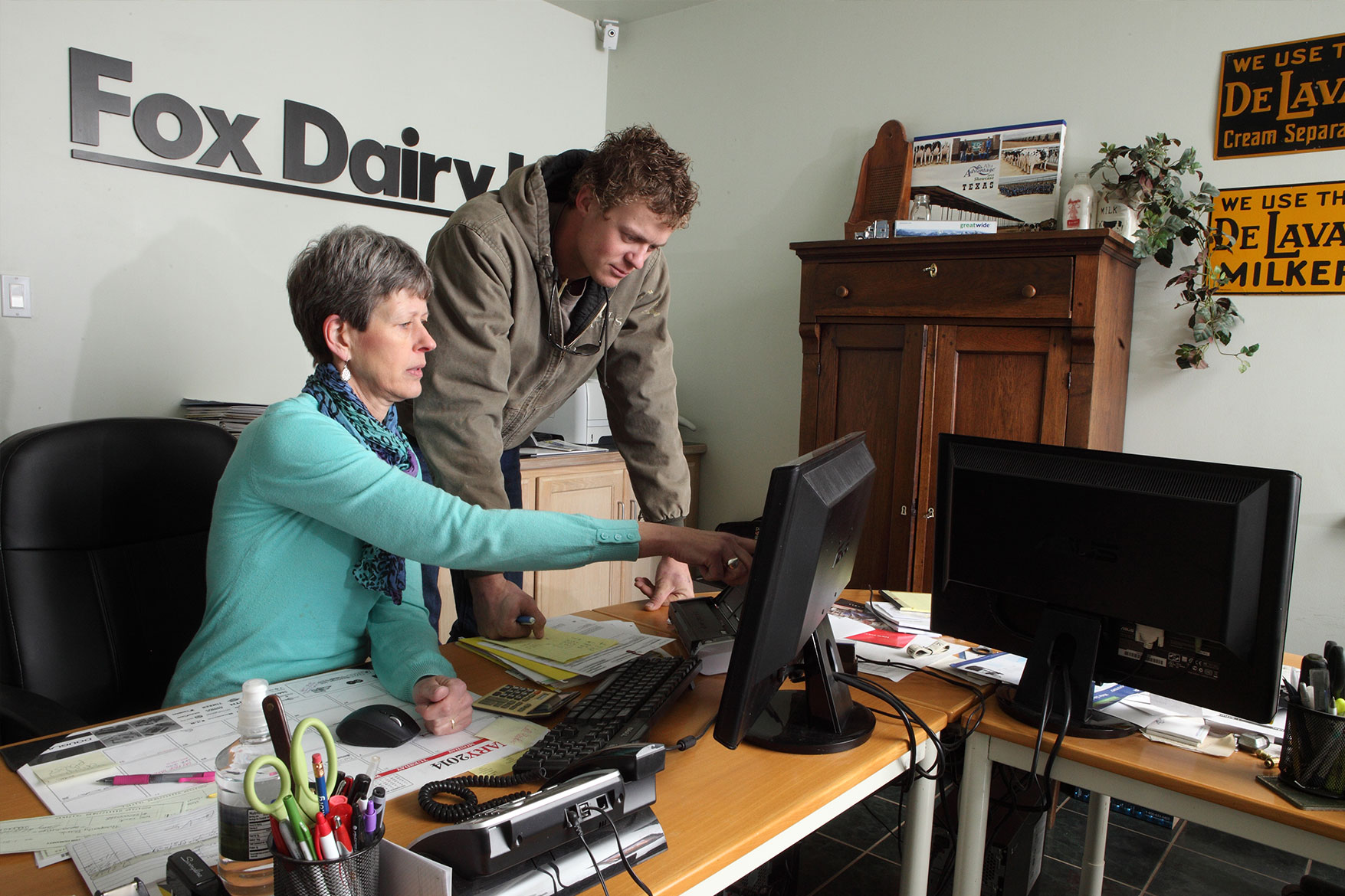 Pauline DeVos and her son look over records at the dairy's office.