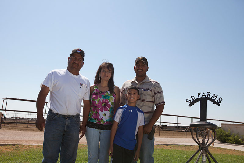 The Vasquez family poses with the SD Farms sign.