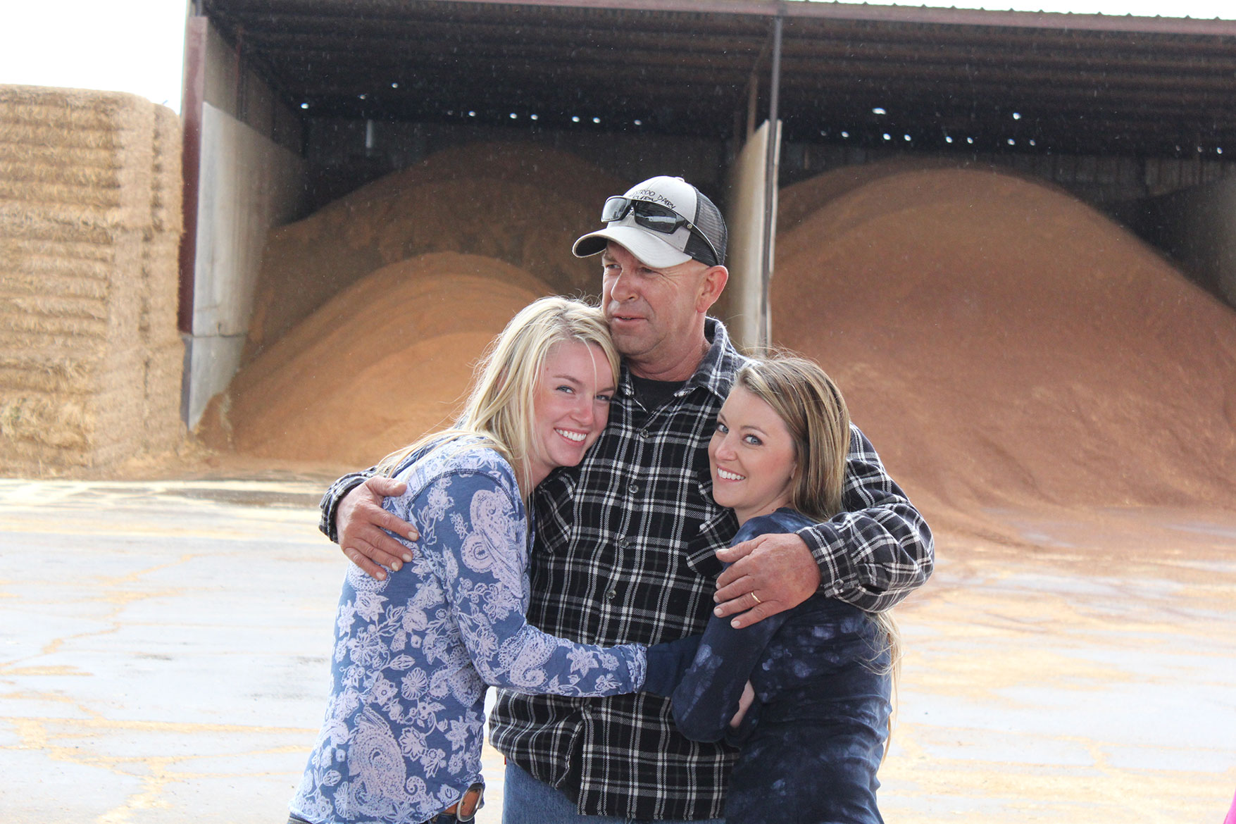 Lexie and Tara give their dad a hug in front of the feed ingredients for the herd.