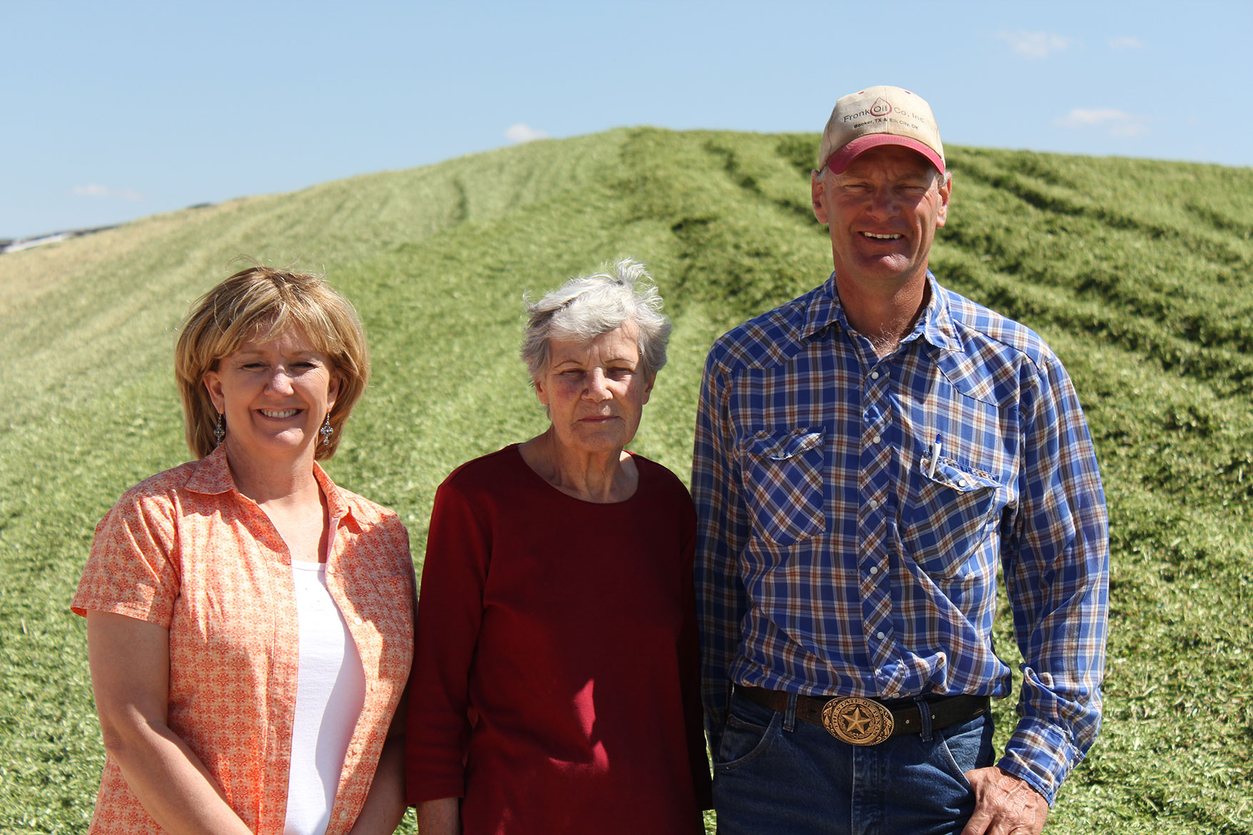 The Mellema family poses in front of the silage (chopped up corn plant) pile at their dairy.