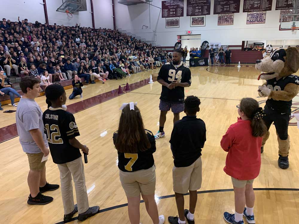 Cam Jordan speaks with a group of students