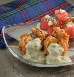chicken fried shrimp with gravy and watermelon salad on a glass plate