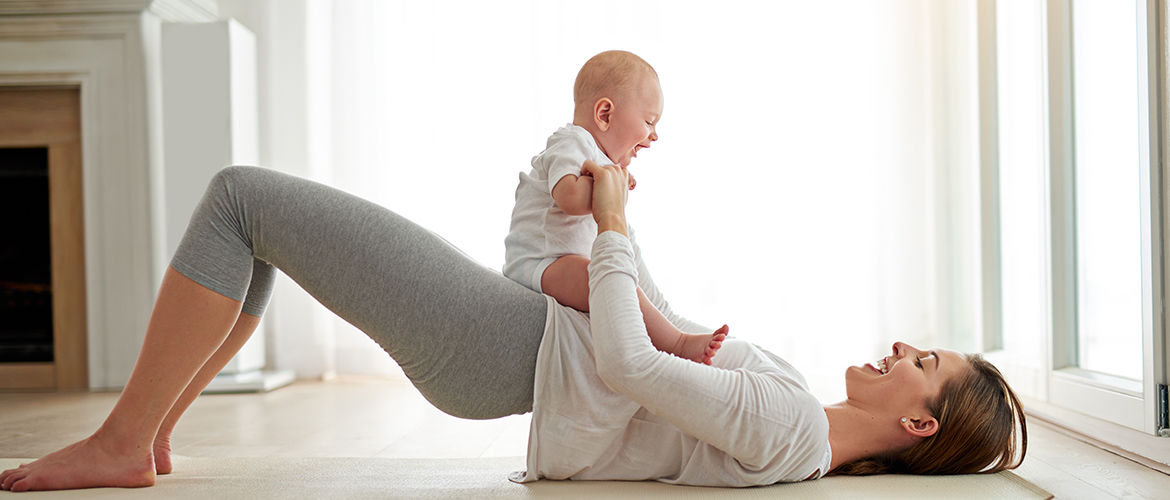 a woman does a glute bridge with her baby