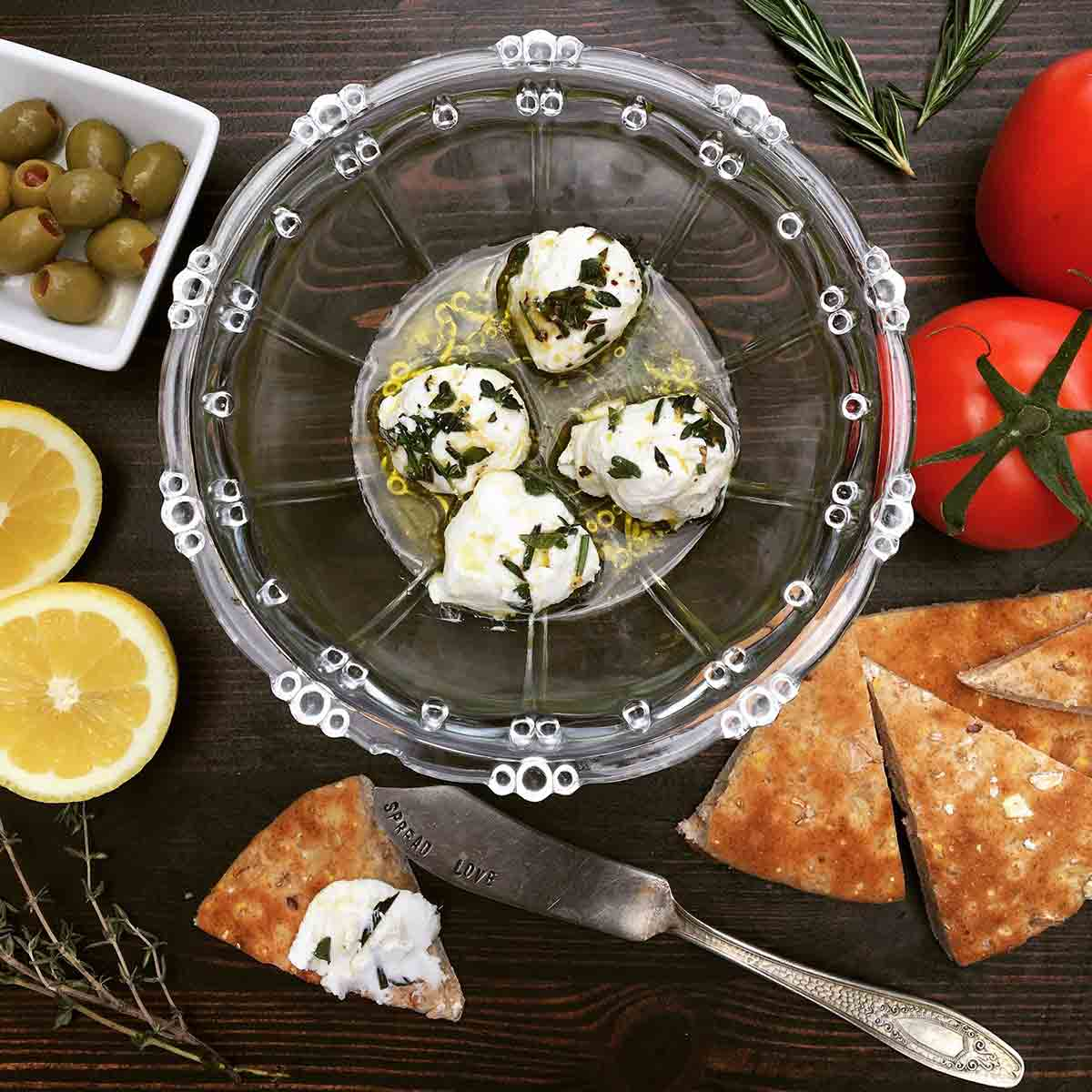 labneh in a bowl with tomatoes and pita bread