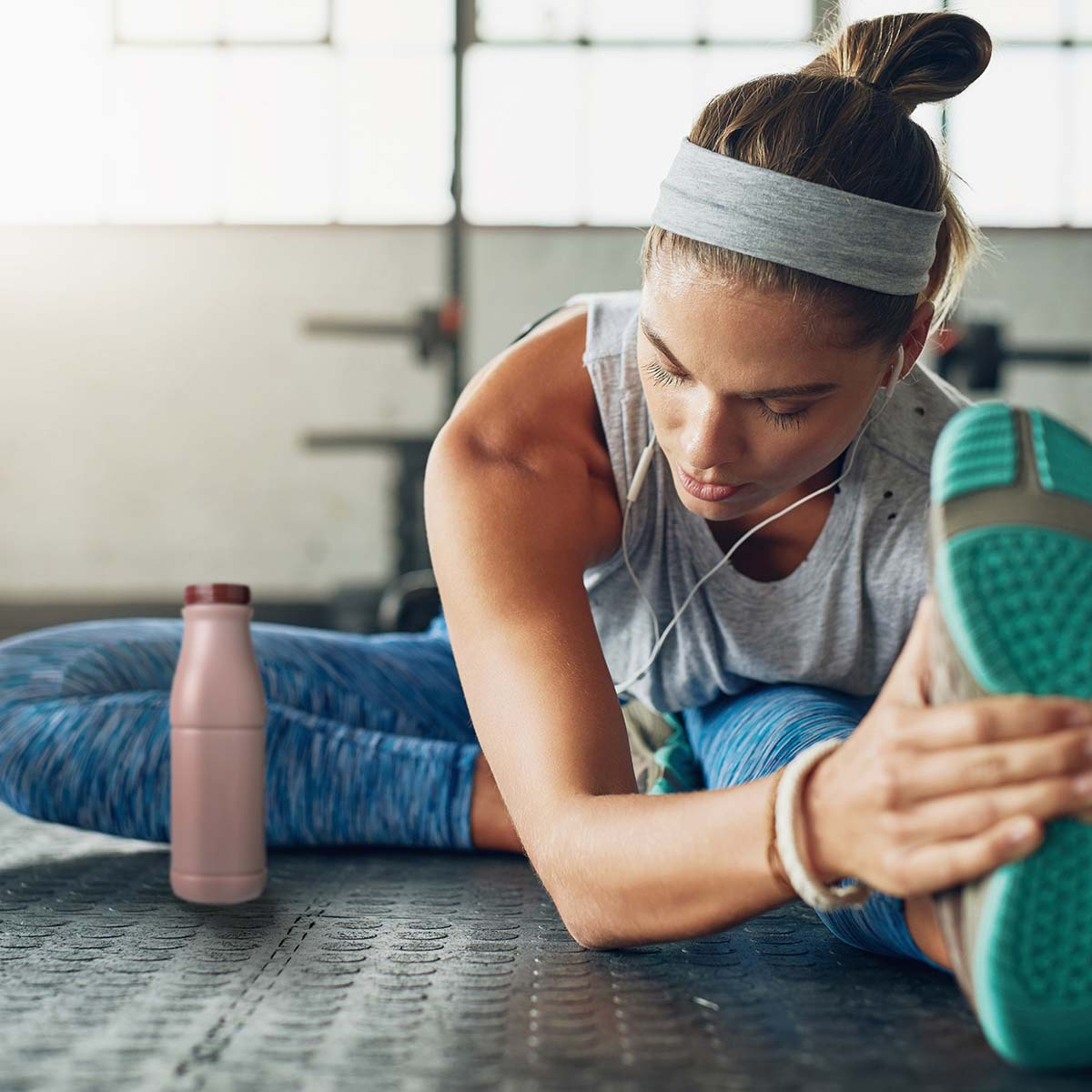 woman in workout clothes stretching her hamstring with a bottle of chocolate milk nearby
