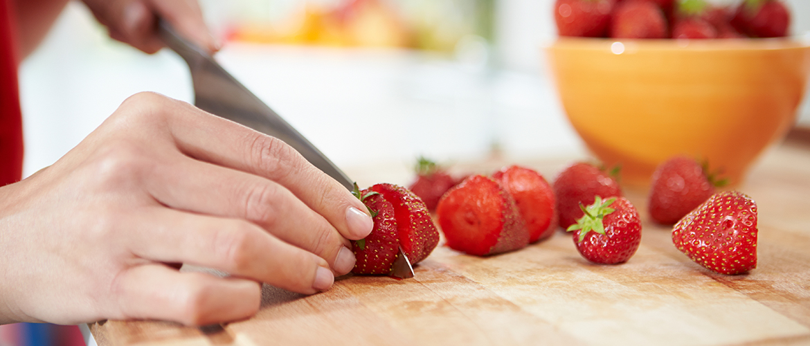 hand cutting a strawberry on a wooden cutting board