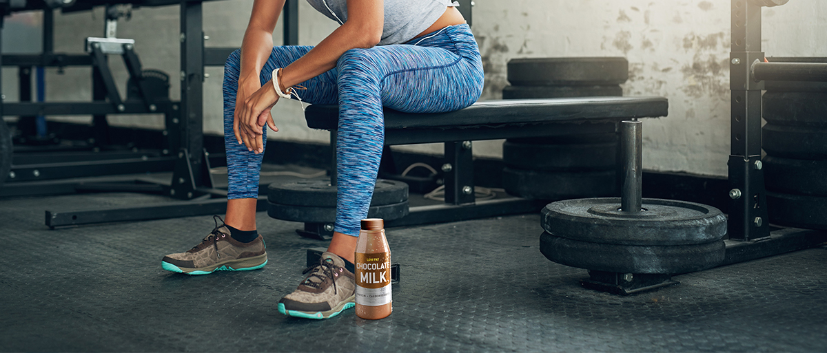 woman working out with chocolate milk nearby