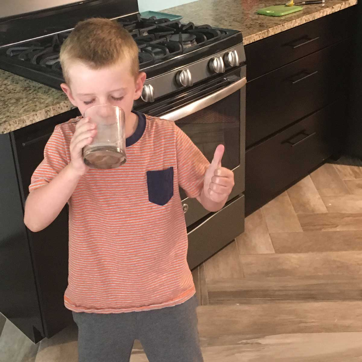 kid drinking milk and giving a thumbs up