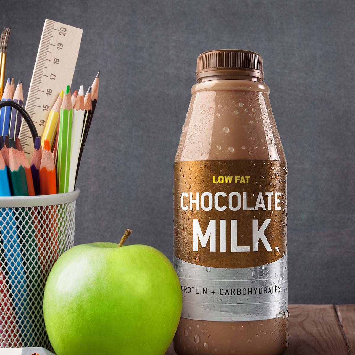 chocolate milk bottle next to an apple and school supplies