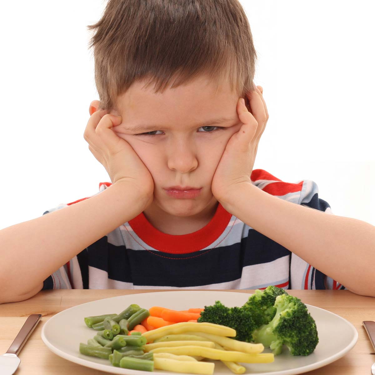kid looking sad over a plate of veggies