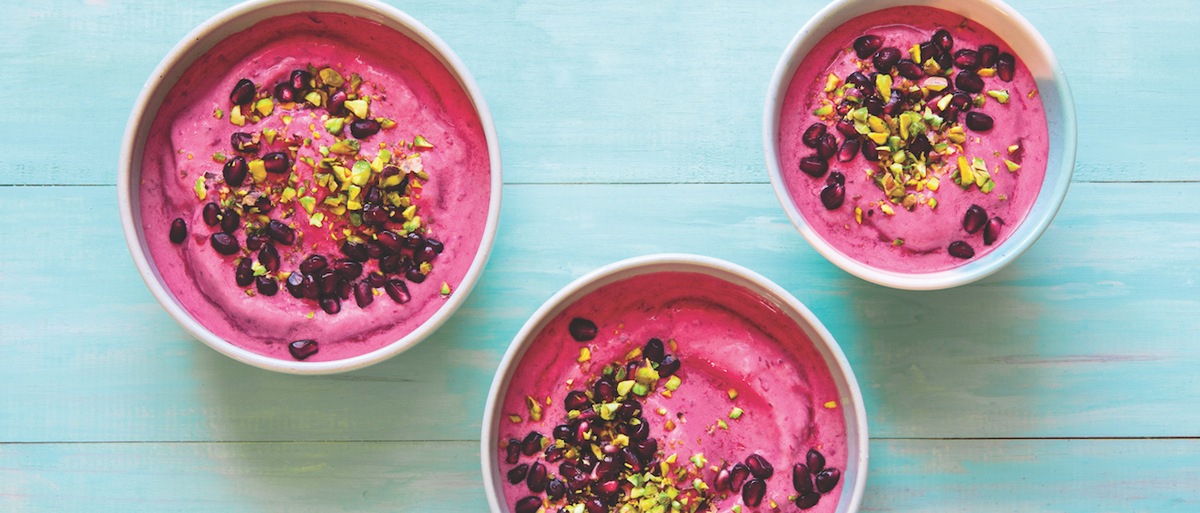 three pomegranate cherry smoothie bowls on a blue background