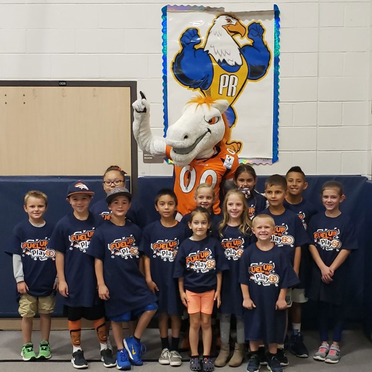 elementary students standing with Miles the mascot in a gym
