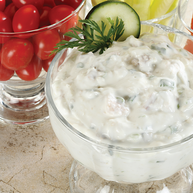 clam dip in a glass serving bowl with dill garnish