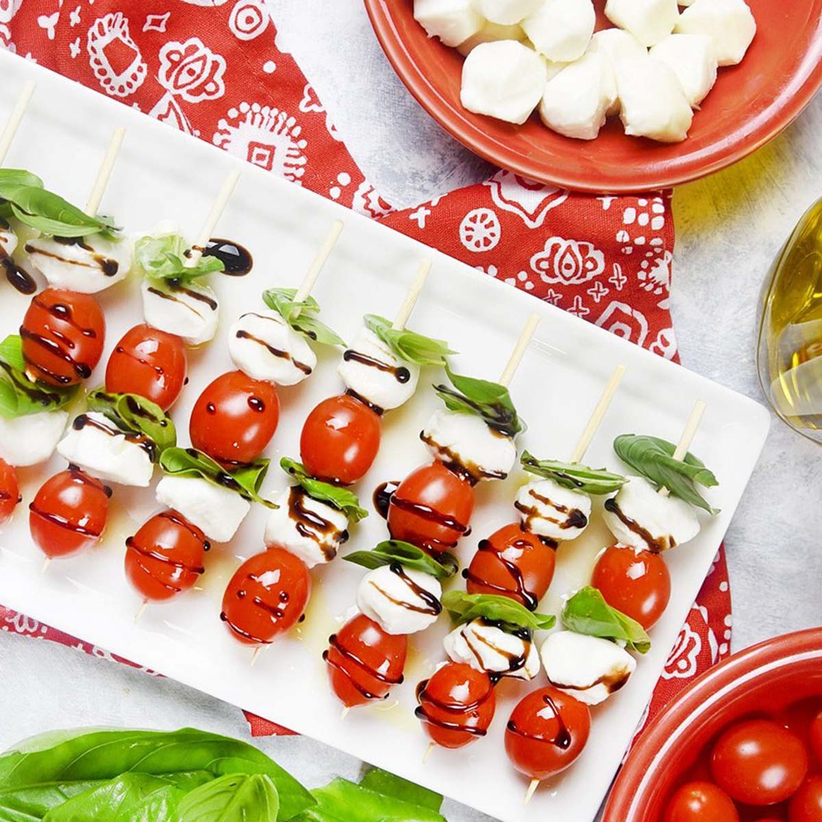 caprese skewers lined up on a plate