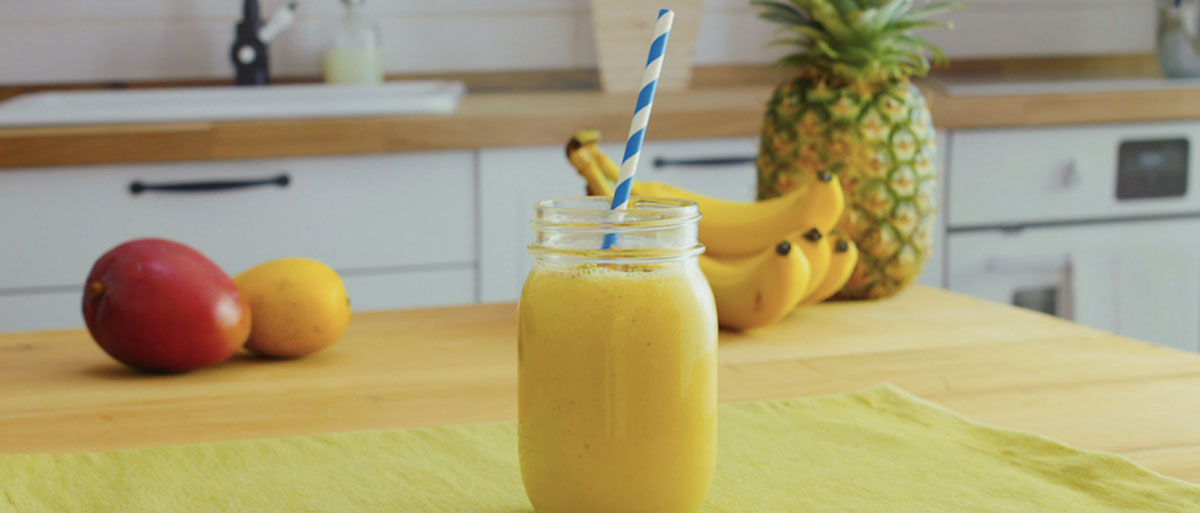 sunshine smoothie with pineapple, banana and mango in the background