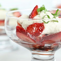 balsamic strawberries in a bowl with ricotta cream topping