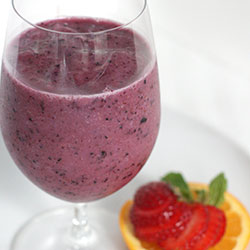 blue smoothie in a glass with a strawberry on the side