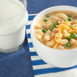 bowl of mac and cheese soup with a glass of milk on the side