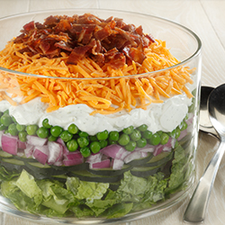 large glass bowl with seven layer salad