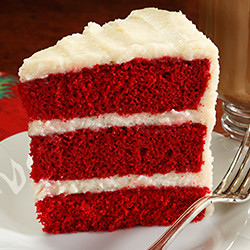 slice of red cake with 3 layers of white frosting