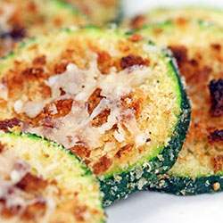 zucchini slices with toasted Parmesan cheese on top