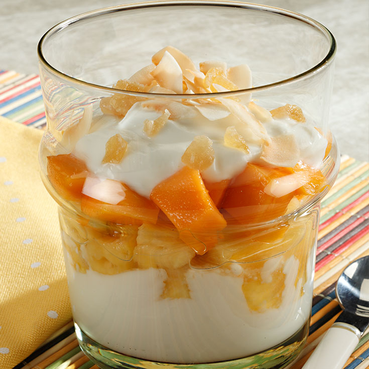 yogurt and tropical fruits layered in a glass dish
