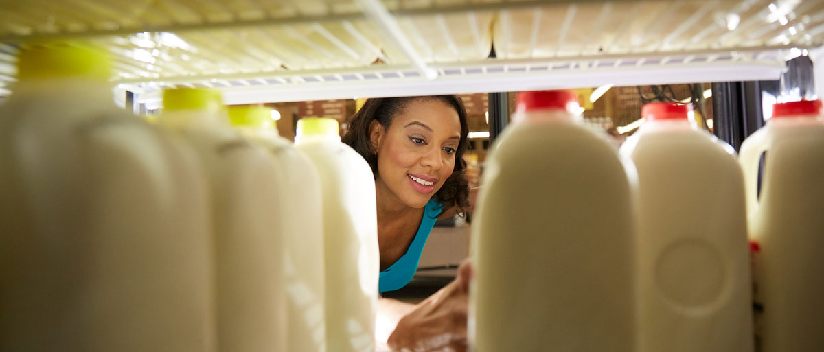 woman looking into the milk case at a grocery store
