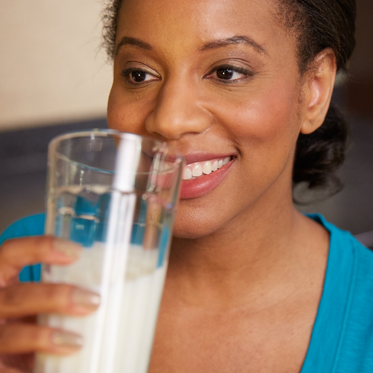 woman drinking a glass of milk and smiling